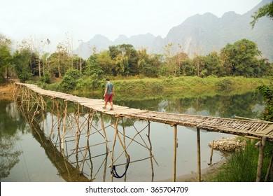 Cheerful Tourist crossing bamboo bridge, limestone view, laos