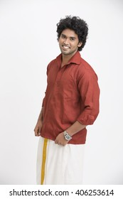 Cheerful traditional south Indian young man posing on white.