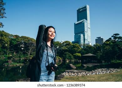 cheerful traveler carrying camera standing outdoor on sunny day flicks hair. young female photographer smiling joyfully enjoying the sunshine. abeno harukas on background in osaka japan.