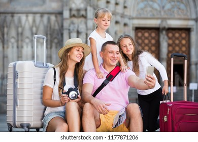 Cheerful travelers family of four strolling on city streets and making selfie