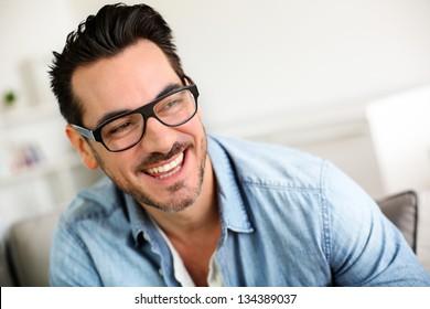 Cheerful trendy guy with black eyeglasses on
