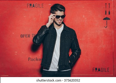 Cheerful and trendy look. Handsome young man adjusting his sunglasses and smiling while standing against red background