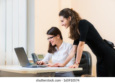 Cheerful two business women working at office with computer