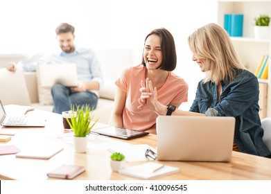 Cheerful two female workers are talking with joy