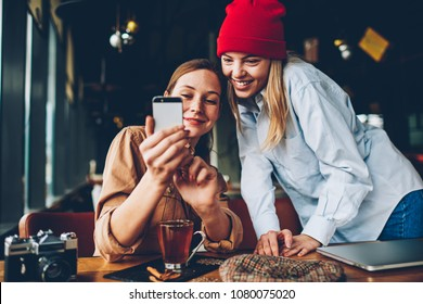 Cheerful two hipsters watching funny videos online on smartphone device connected to 4G internet.Positive teenagers checking social networks on mobile phone resting together in cafe interior