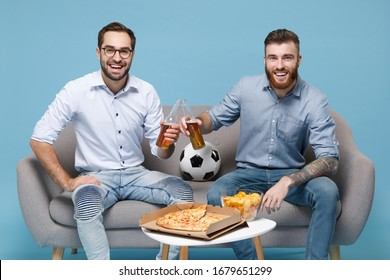Cheerful two young men guys friends colleagues in casual shirt sit on couch isolated on pastel blue background. Sport leisure concept. Cheer up support favorite team with soccer ball hold beer bottle