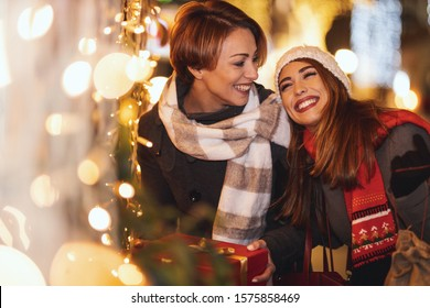 Cheerful two young women are having fun in the city street at the Christmas night. They are laughing and buying presents for their darlings.