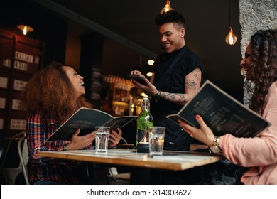 Cheerful two young women sitting at cafe holding menu card giving order to waiter. Young woman placing order to a waiter at restaurant while sitting with her friend.