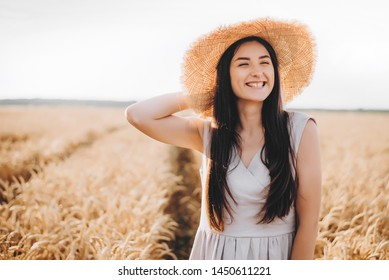 cheerful ukrainian young woman on the field at sunset. portrait of a pretty girl who is walking around the field. selective focus