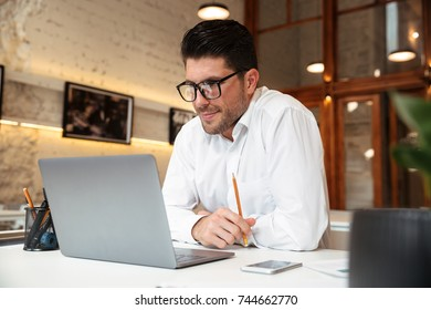 Cheerful unshaven businessman in white shirt looking at laptop screen in office