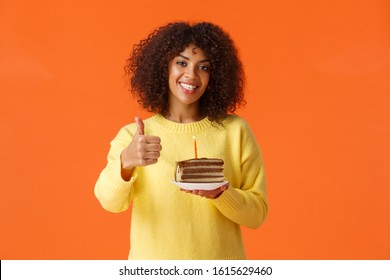 Cheerful upbeat african-american b-day girl having awesome birthday party, blow candle, holding plate with delicious cake, showing thumbs-up satisfied and smiling happy, orange background