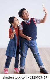 Cheerful Vietnamese boy and girl talking selfie on smartphone