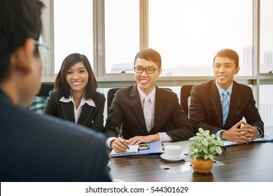 Cheerful Vietnamese business people conducting interview with candidate