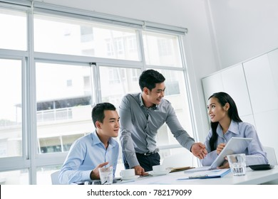 Cheerful Vietnamese colleagues discussing information on tablet screen