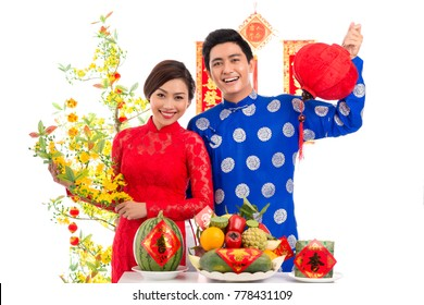 Cheerful Vietnamese couple wearing traditional costumes looking at camera with toothy smiles while holding attributes for celebrating Lunar New Year