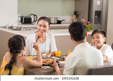 Cheerful Vietnamese family of four eating traditional food at dinner