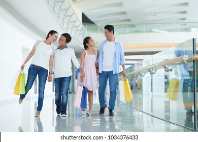 Cheerful Vietnamese family of four walking in mall with many shopping bags