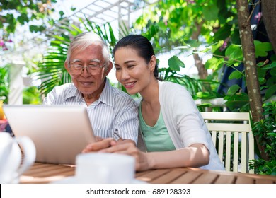 Cheerful Vietnamese father and daughter sitting in outdoor cafe and watching something on tablet computer