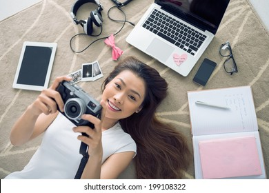 Cheerful Vietnamese girl lying on the floor  with her camera in hands