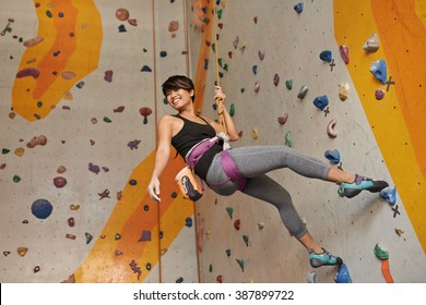 Cheerful Vietnamese girl practicing climbing on rock wall indoors