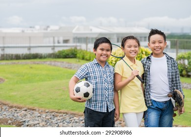 Cheerful Vietnamese kids with sports equipment standing outdoors