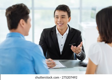Cheerful Vietnamese sales manager giving advice to his clients