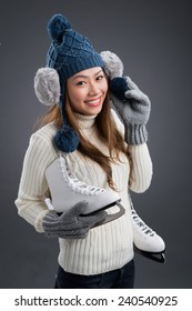 Cheerful Vietnamese woman with figure skates smiling and looking at the camera