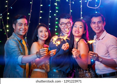Cheerful Vietnamese young people with burning sparklers in hands