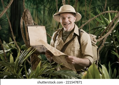 Cheerful vintage explorer in the jungle with map and blank sign.