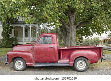 Cheerful vintage red truck parked in front of white Victorian home