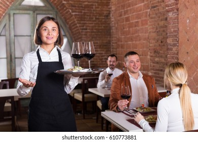 Cheerful waiter showing country restaurant to visitors