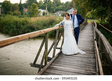 Cheerful wedding couple on wooden bridge at sunset.