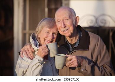 Cheerful white senior couple holding coffee mugs