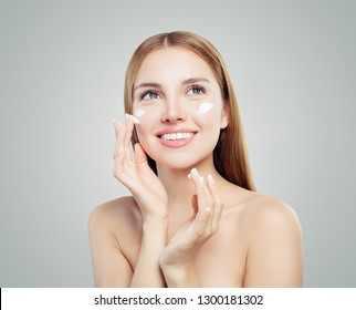 Cheerful woman applying facial cosmetic cream and smiling on white background. Beautiful female model portrait