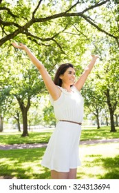 Cheerful woman with arms raised against trees in park