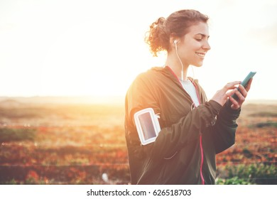 Cheerful woman athlete using mobile phone outdoors. Listening music near the nature meadow. Sunrise time