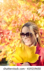 Cheerful woman with autumn leaves in her hands in autumn park