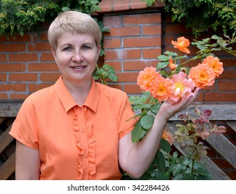 The cheerful woman of average years shows a rose hand in a garden