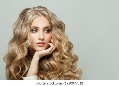 Cheerful woman with blonde curly hairstyle on white background