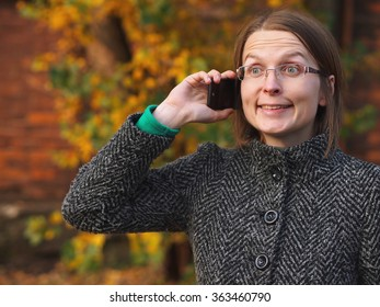 Cheerful woman calling in the autumn nature.