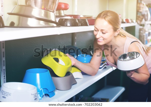 Cheerful  woman choosing through different bowls for pets in pet shop