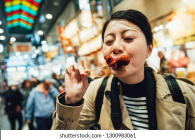 cheerful woman closing eyes trying local japanese street food in nishiki ichiba kyoto japan. young girl tourist eating small octopus snack in brocade market. beautiful lady experience cuisine.