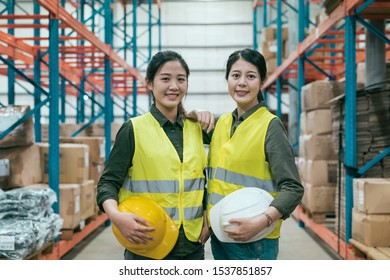 Cheerful woman coworkers of warehouse smiling and looking at camera. confident lady colleagues in stockroom posing with carrying hard hat. best team work partner in storehouse lifestyle concept.