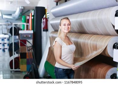 cheerful woman customer choosing linoleum flooring in housewares hypermarket