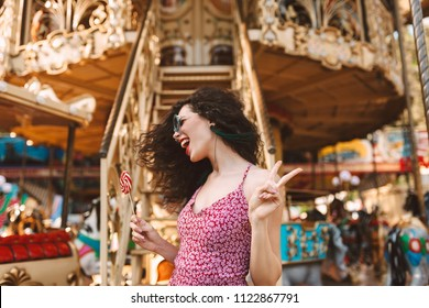 Cheerful woman with dark curly hair in sunglasses and dress standing with lolly pop candy in hand and happily looking aside while spending time in amusement park