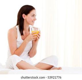 Cheerful woman drinking an orange juice sitting on her bed at home