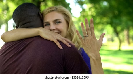 Cheerful woman embracing future husband and showing engagement ring, couple