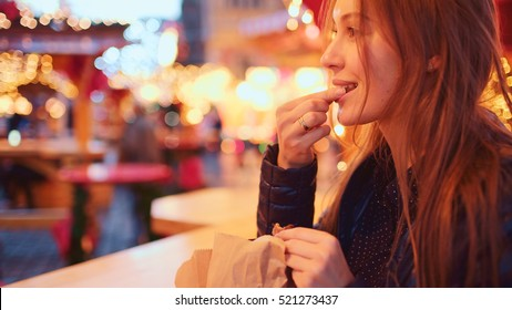 Cheerful Woman Enjoying European Christmas Market. 4K. Happy Girl eating hot roasted chestnuts, Winter Fair Holiday Season. Blurred Christmas Lights on background, dusk.