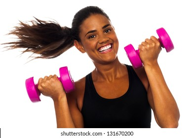 Cheerful woman exercising and building up biceps using dumbbells.