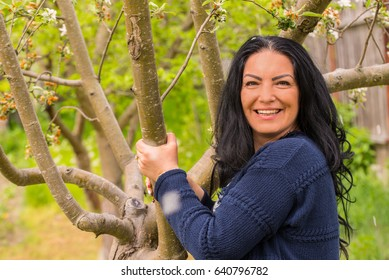 Cheerful woman in garden holding hands on apple tree